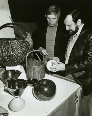 "Olaf Harringer (left), exhibits manager at the Museum of Science and Industry in Chicago, and Theodor J. Swigon, assistant exhibits manager, inspect pottery, glassware, textiles, and other pieces from the ""Artist-Craftsmen of the Federal Republic of Germany"" exhibit."